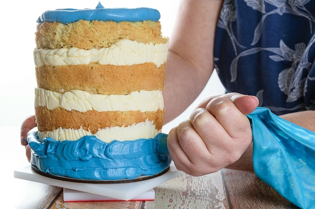 High key photo. baker using a icing nozzle to put blue frosting on the base of the cake.