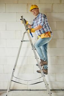 High ladder as a support for carpenter worker