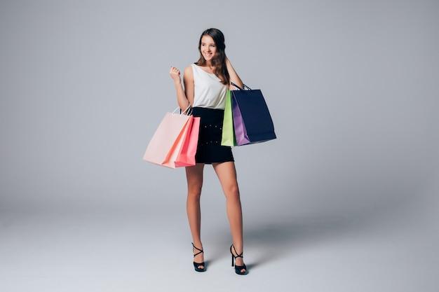 Высокая дама в туфлях на высоких каблуках держит разные бумажные пакеты для покупок, изолированные на белом