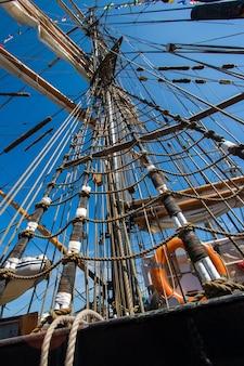 青い空を背景に帆とロープのはしごを備えた高いマスト