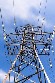 구름 산업과 에너지가 있는 푸른 하늘 배경에 있는 전력선의 높은 금속 기둥
