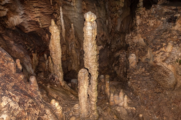 High mineral stalagmites inside the dark cave