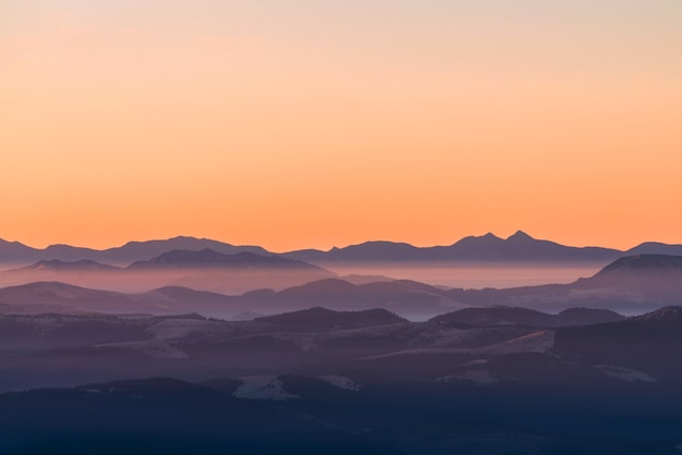짙은 안개 속의 높은 산맥. 일몰 동안 안개 속에서 산의 층. 다층 안개 산맥.