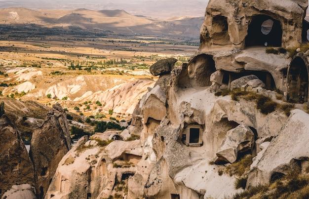 Uchisarのトルコの風景の背景に洞窟の家と高山