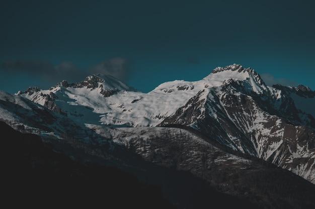 저녁에 눈으로 덮여 높은 산