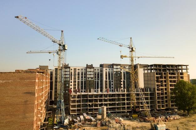 Строящиеся высокие многоэтажные жилые дома. бетонный и кирпичный каркас многоэтажного жилья. девелопмент недвижимости в городской местности.