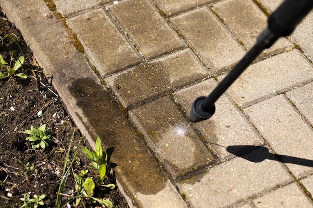 Мойка высокого давления очищает бетонный пол струей воды.
