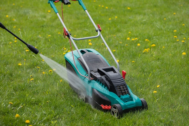 High-pressure washer washes lawn mower with jet of water