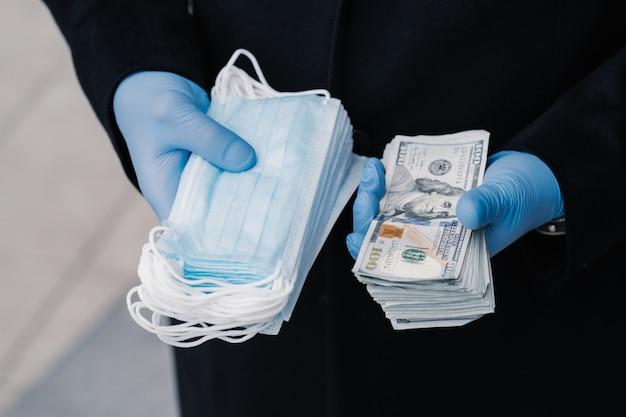 High price on medical masks. shortage of virus masks needed during quarantine. unrecognizable man has profitable business selling face masks during global pandemic, holds many dollars banknotes