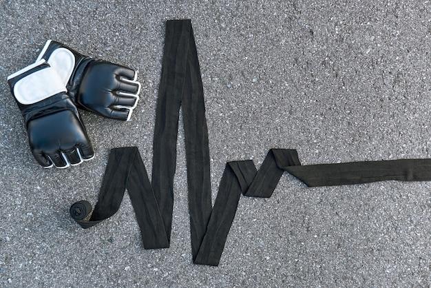 높은 맥박수. 아스팔트 배경에서 권투 붕대가 있는 스포츠 권투 장갑의 클로즈업