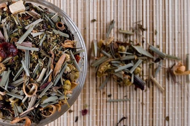 Травяной чай высокого качества в стеклянном крупном плане на соломенном фоне
