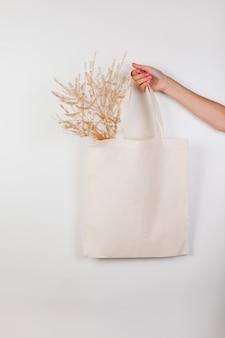 고급스러운 고급 캔버스 토트백 모형 흰색 가방은 장식이 있는 흰색 격리된 배경에 만들어졌습니다.