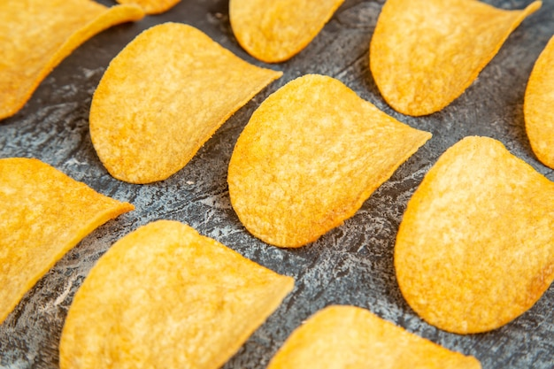 High resolution photo of crunchy baked five chips lined up in rows on gray table