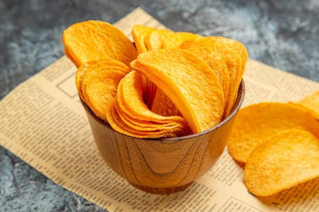 Foto ad alta risoluzione di deliziose patatine fatte in casa sul giornale sul tavolo grigio