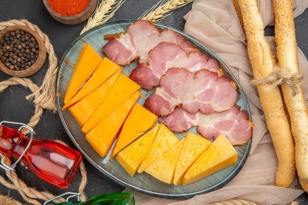Foto ad alta risoluzione di deliziosi snack bottiglie cadute peperoni su asciugamano e corda su sfondo nero