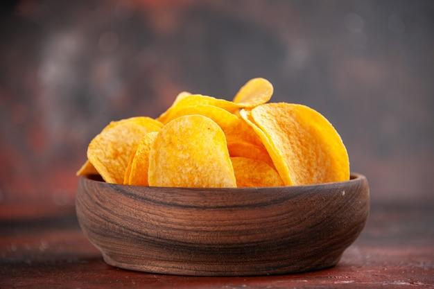 Foto ad alta risoluzione di deliziose patatine croccanti fatte in casa in una piccola ciotola marrone su sfondo scuro