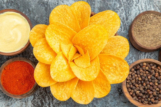 High resolution photo of homemade potato chips decorated like flower shaped in a brown bowl on gray table