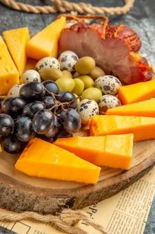 古い新聞の木製の茶色のトレイロープにさまざまな果物や食べ物と最高のスナックの高解像度写真