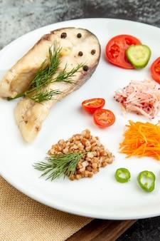 氷の表面の木のまな板の上に裸のタオルの上に白い皿に緑の野菜を添えた、ゆでた魚のそば粉の高解像度写真