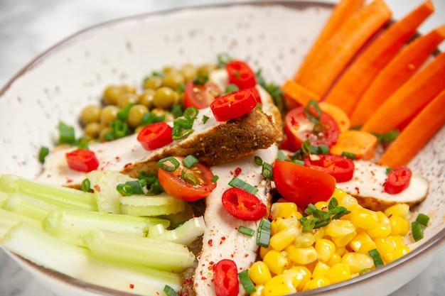 空きスペースのある白い表面の皿にさまざまな具材が入ったおいしいサラダの高解像度写真