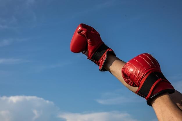曇った青い空に赤いボクシンググローブを持っている男性の手の高解像度写真。