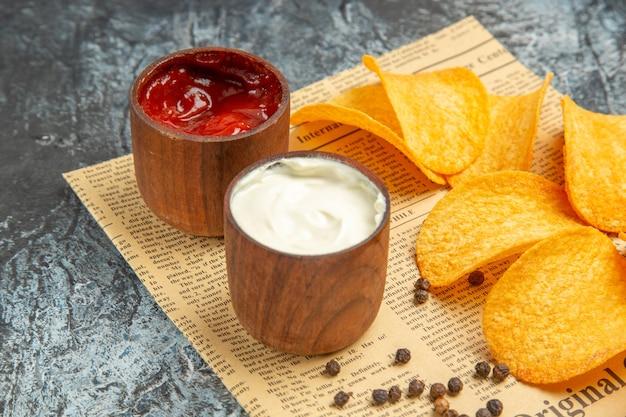 Vista ad alta risoluzione di deliziose patatine fatte in casa e ketchup maionese ciotola di pepe sul giornale sul tavolo grigio