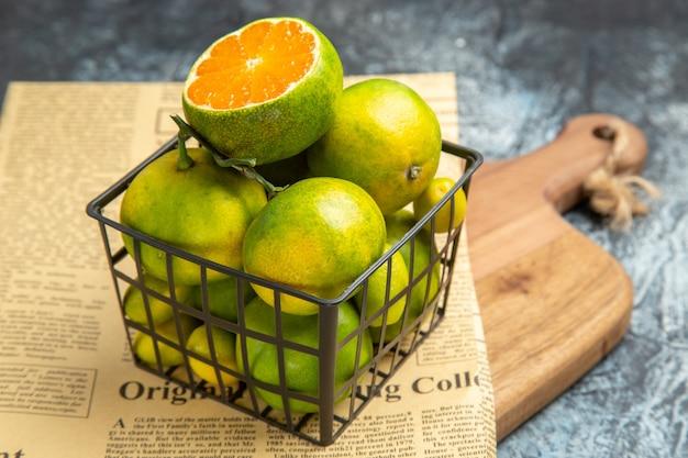 Vista ad alta risoluzione di agrumi freschi in un cesto di giornale su tagliere di legno su sfondo grigio
