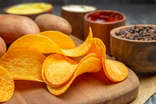 High resolution view of homemade delicious potato chips on wooden cutting board different spices and flavors on newspaper on gray table