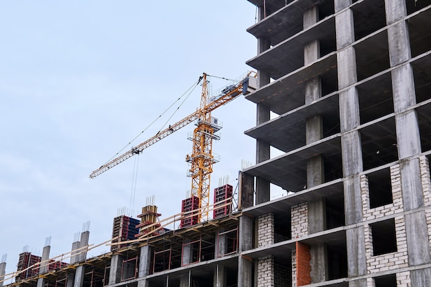 High-rise building under construction and crane against the sky