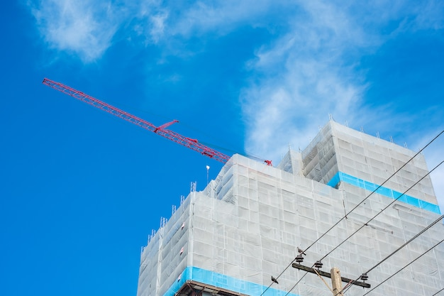 High rise building construction site with crane on blue sky