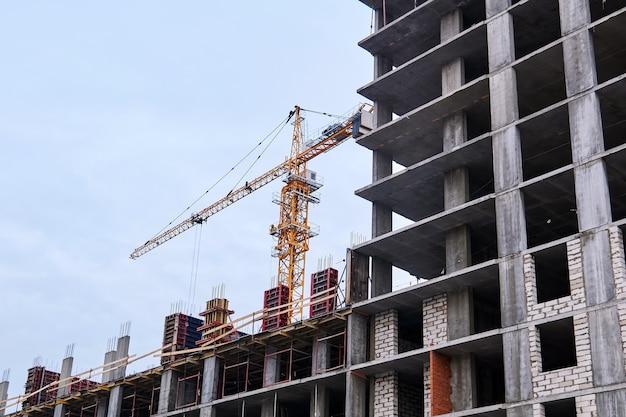 建設中の高層ビルと空を背景にクレーン