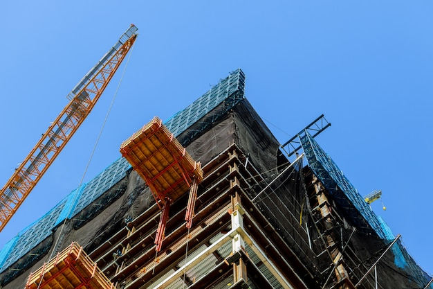 High-rise crane supplies material to a high-rise building construction site with two cranes
