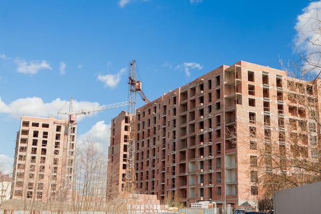 建設中の高層高層ビル。建物の近くのタワークレーン。活動、建築、開発プロセス、超高層ビル。