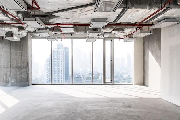 High rise office under construction with open ceiling to see structure and system work, glass windows for take aerial view of buildings in the city. empty space for developer investment.