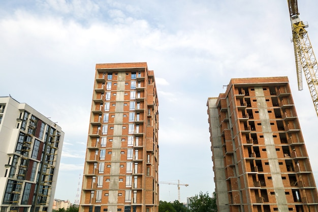 На строительной площадке строятся высотные жилые дома и башенный кран. развитие недвижимости.