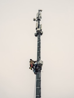 A high-rise worker works on a cell tower.