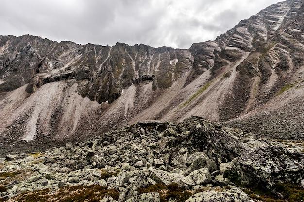 Высокая скала на фоне облачного неба и груды камней на переднем плане. мох на камнях. по горизонтали.