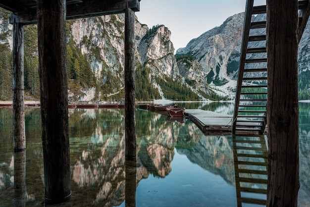 High rocky mountains reflected in braies lake with wooden stairs near the pier in italy
