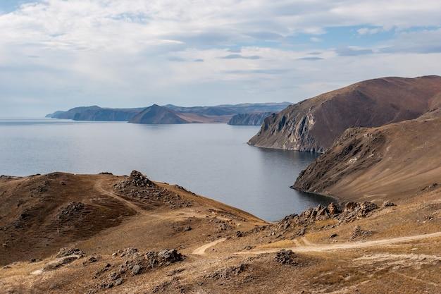 道路のあるバイカル湖の高い岩の多い海岸は湖に下ります