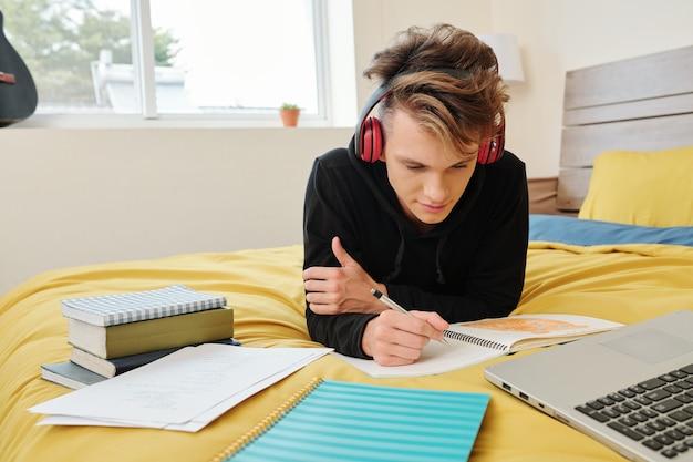 Старшеклассник лежит на кровати дома и пишет в тетрадке, делая домашнее задание для класса математики
