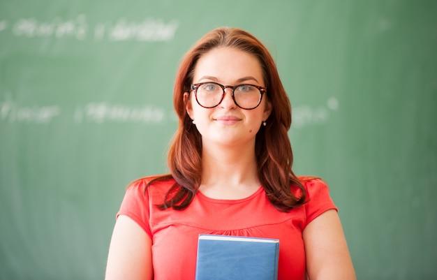 Ученик средней школы стоит перед классной доской