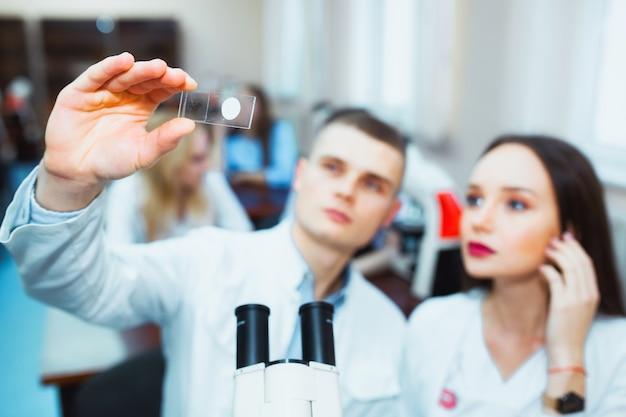 Учащиеся средней школы, глядя через микроскоп в классе биологии. молодой ученый проводит исследования.