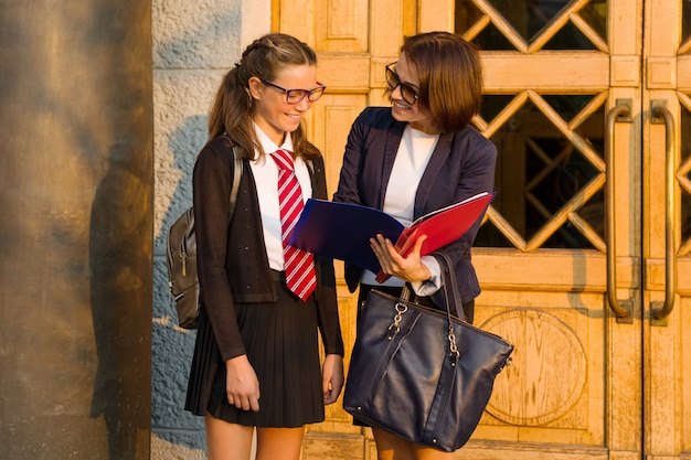 高校の先生が学校の正面玄関近くで女子学生と話しています。