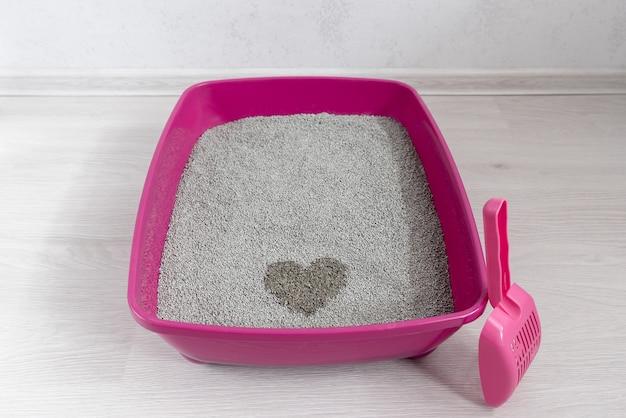ベントナイト吸収剤と部屋のスクープを備えたハイサイド猫用トイレトレイ Premium写真