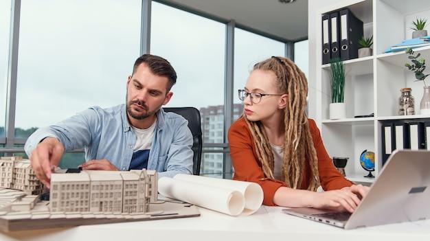 미래 건물의 모형을 작업하는 숙련 된 열심히 일하는 창의적인 남녀 디자이너