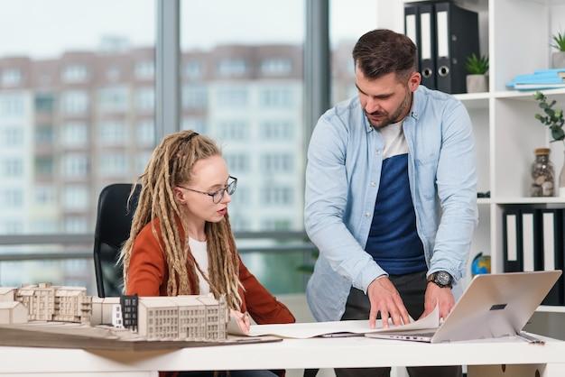 将来の建物のモックアップを扱う、熟練した勤勉で創造的な男性と女性のデザイナー