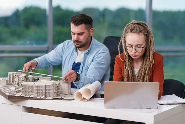 High-skilled hardworking creative male and female designers working with mock-up of future buildings