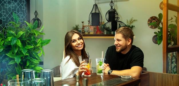 술집에서 칵테일을 마시 며 즐거운 시간을 보내는 상류 사회 사람들. 웃는 아름 다운 커플