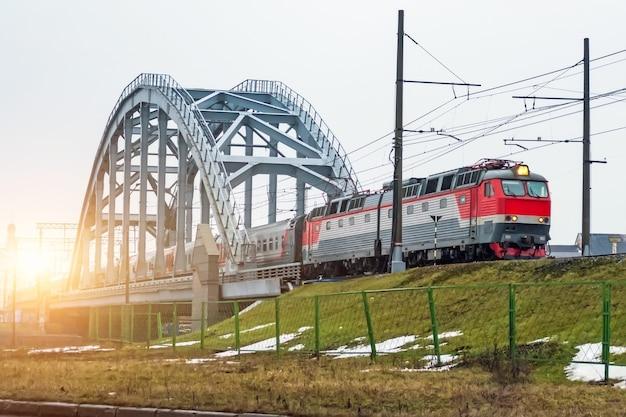 日没の夕方に橋の工業鉄道を急いでいる高速の赤い旅客列車。
