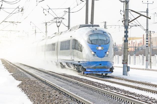 Скоростной поезд зимой на большой скорости едет по заснеженной местности.